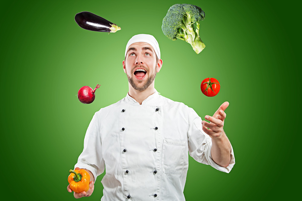 Ein Koch jongliert Gemüse vor einem grünen Hintergrund.