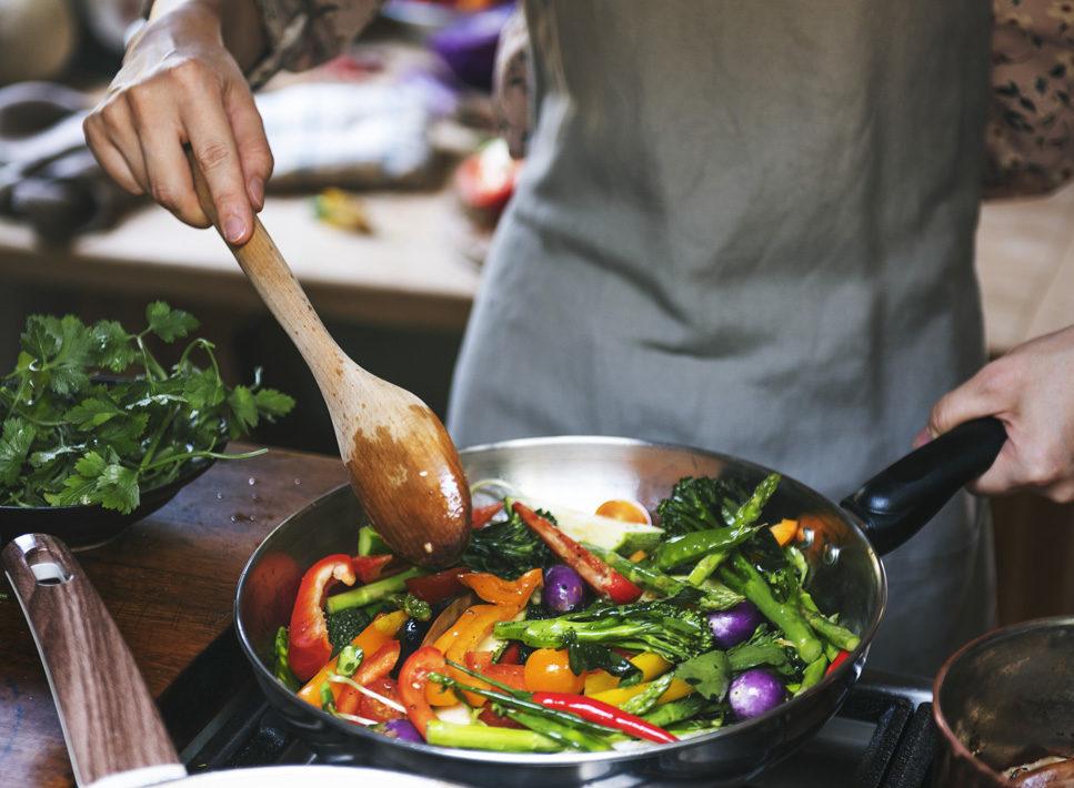 Ein Koch brät Gemüse in einer Pfanne